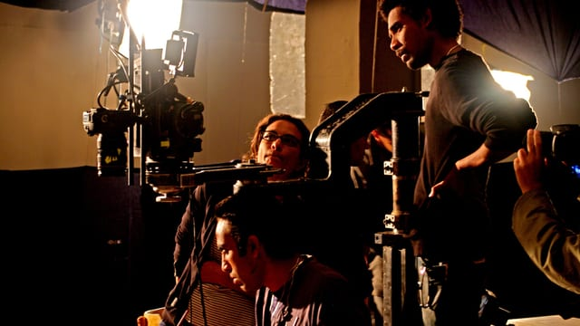 Hala Elkoussy sitzt hinter der Kamera bei einem Filmdreh, neben ihr sind zwei Mitarbeiter, die konzentriert bei der Arbeit sind.