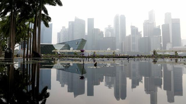Die Skyline von Singapur spiegelt sich im See.