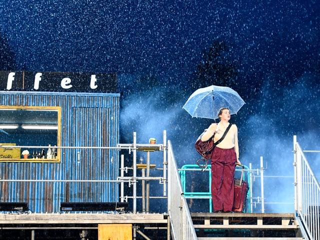 Eine Schauspielerin steht bei ströhmendem Regen auf der Bühne.