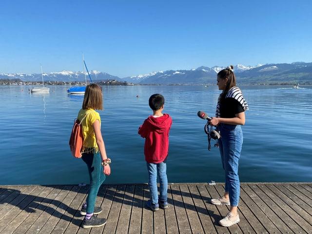Ylva, Patrick und Angela stehen auf einem Steg und blicken auf den Zürichsee.