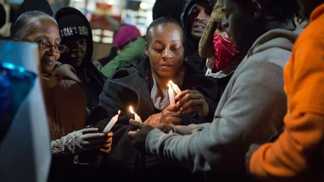 Vier Frauen zünden für den Toten Kerzen an.
