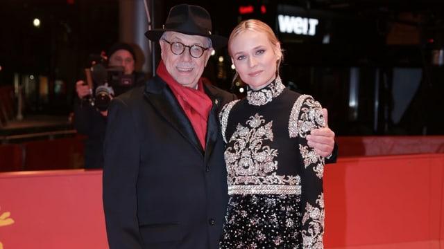 Ein Mann mit Hut hält eine elegante Frau im Abendkleid