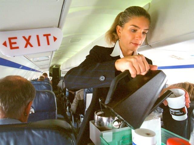 Flight Attendant serviert Kaffee während eines Fluges. Sie ist sehr konzentriert bei der Arbeit.