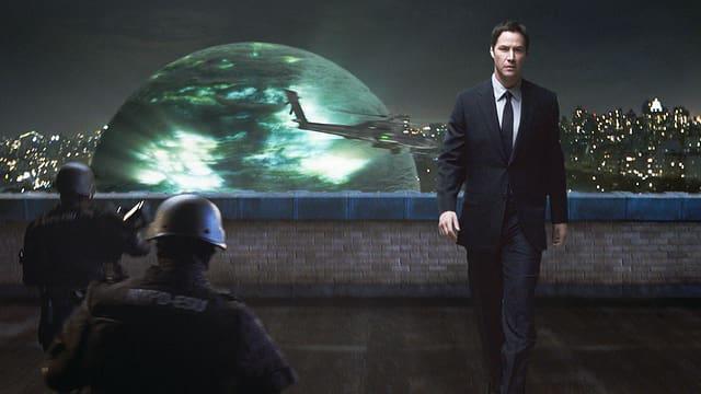 Ein Mann im Anzug geht auf einem Hausdach. Auf dem Dach sind Soldaten zu sehen. Im Hintergrund ist eine riesige, leuchtende Kugel und ein Kampfhubschrauber zu sehen.