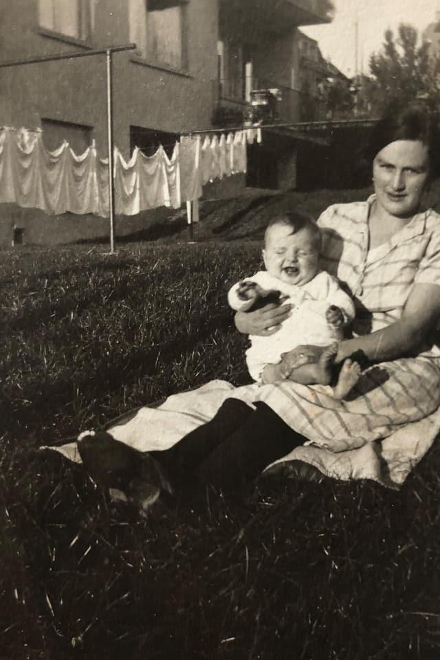 Die Mutter sitzt auf einer Wiese und hält Baby-Betli im Arm.