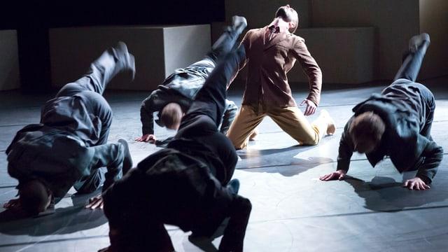 Fünf Tänzer vornüber gebeugt mit Stirn am Boden einer entgegengesetzt zum Himmel gestreckt.