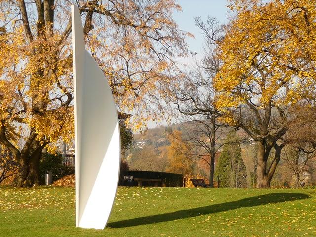 Weisse, geometrische Skulptur in einem herbstlichen Garten.