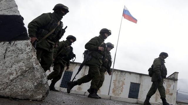 Uniformierte vor einem Armeegebäude mit der russischen Flagge.