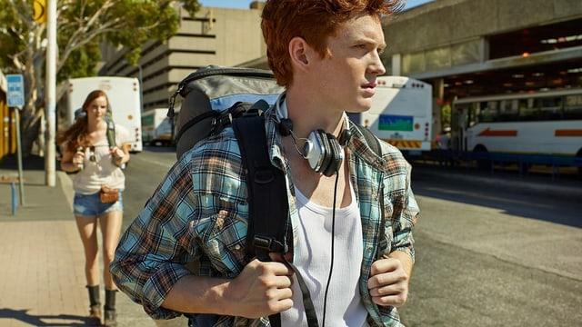Ein junger Mann mit Rucksack und Kopfhörer läuft eine Strasse entlang, hinter ihm geht eine junge Frau ebenfalls mit Rucksack.