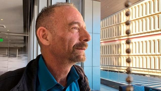 Mann mit Bart und lichtem Haar in Krankenhaushalle