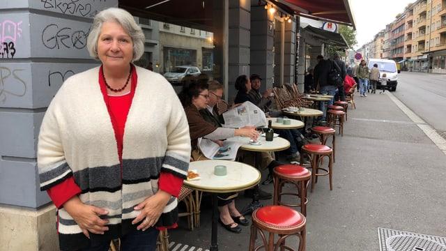 Eine Frau steht vor einem Caffè.