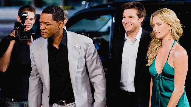 Zwei edel gekleidete Männer und eine blonde Frau im Abendkleid an einer Gala-Veranstaltung.