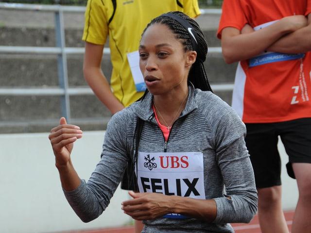 Die US-amerikanische Sprinterin Allyson Felix erklärt den Kindern ihr Startritual