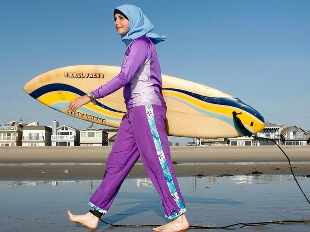 Eine Frau in einem Ganzkörperbadeanzug und einem Surfbrett unter dem Arm.