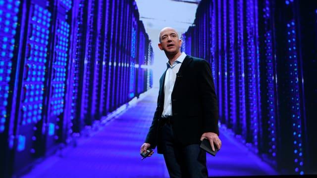 Amazon Gründer Jeff Bezos steht vor dem Foto eines Rechenzentums.