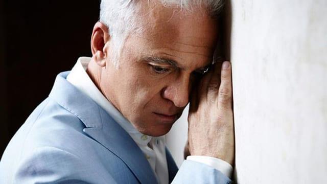 Mann lehnt traurig an Wand.