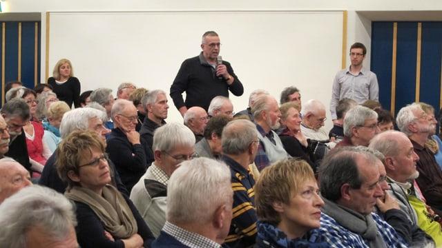 Blick ins Publikum. Im Hintergrund ein Mann mit Mikrofon, der ein Statement abgibt.