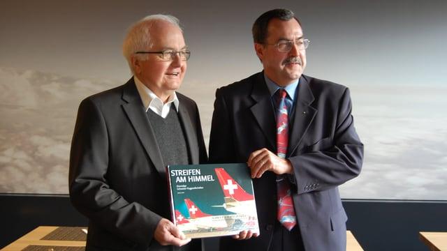 Aviatiker und Buchautor Markus Seiler hält sein neues Buch in den Händen, neben ihm Verleger Hansjörg Bürgi.