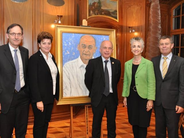 Eine Gruppe von fünf Leuten steht aufgereiht vor einem Bild, das Ueli Maurer zeigt.