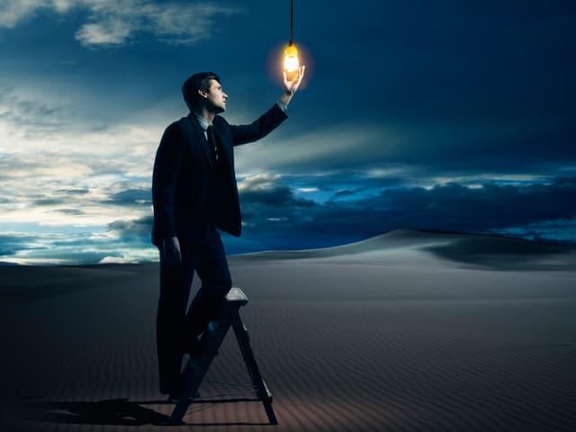 Ein Mann steht auf einer Leiter in der Wüste und hält seine Hand an eine brennende Glühbirne, die vom Himmel herunterhängt.