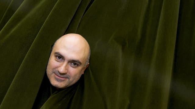 Der Kopf von Regisseur Calixto Bieito vor einem grünen Theater-Vorhang
