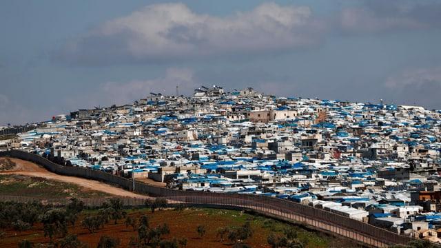 Hütten- und Zelte ohne Ende auf einem Hügel, daneben eine meterhohe Grenzbefestigung.