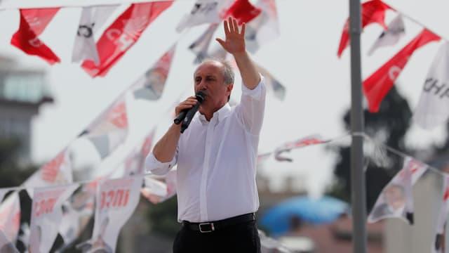 Mann in weissem Hemd auf einer Bühne spricht in ein Mikrofon, den linken Arm erhoben.
