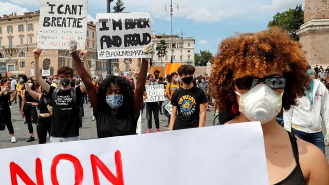 Demonstranten mit Gesichtsmasken halten Plakate in der Höhe.