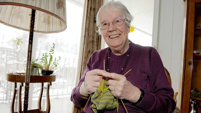 Eine ältere Frau sitzt in einer Stube und strickt.