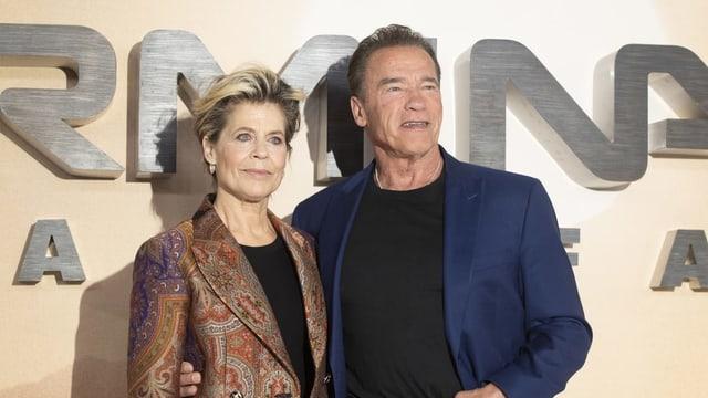 Eine ältere Frau und ein älterer Mann posen vor einer Terminator Schrift.