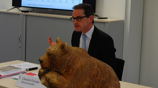 Holzbär und Mann am Tisch