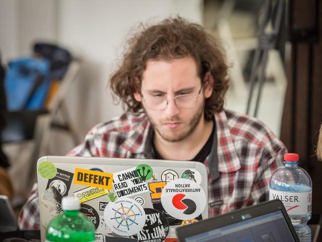 Ein Teilnehmer des Hackathons sitzt vor seinem Laptop, der mit bunten Aufklebern beklebt ist.