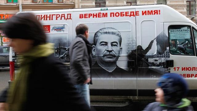 Ein weisser Bus, der auf der Seitentüre ein schwarz-weiss-Porträt von Stalin zeigt.