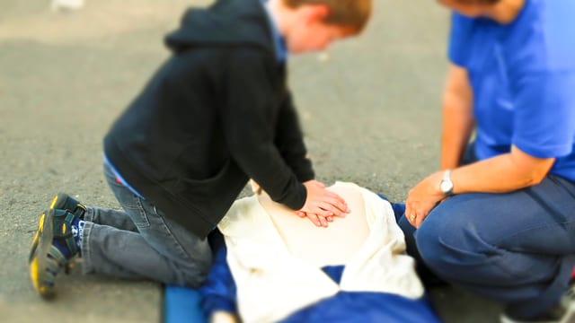 Ein Junge übt an einer Puppe Herzmassage