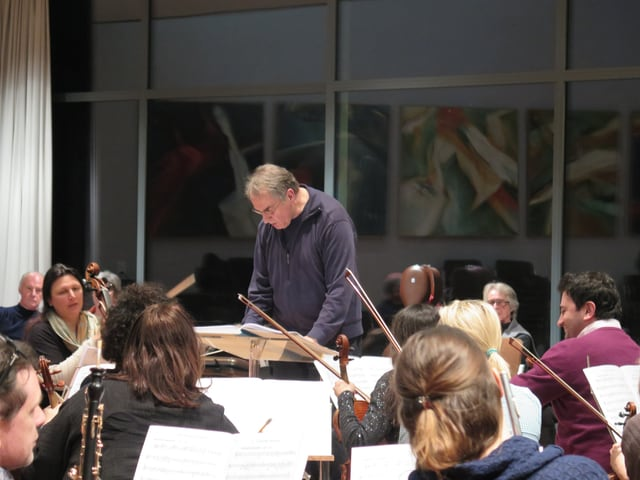 Dirigent starrt konzentriert in seine Noten.
