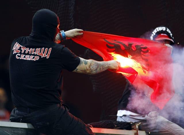 Ein serbischer Hooligan verbrennt eine kosovarische Flagge