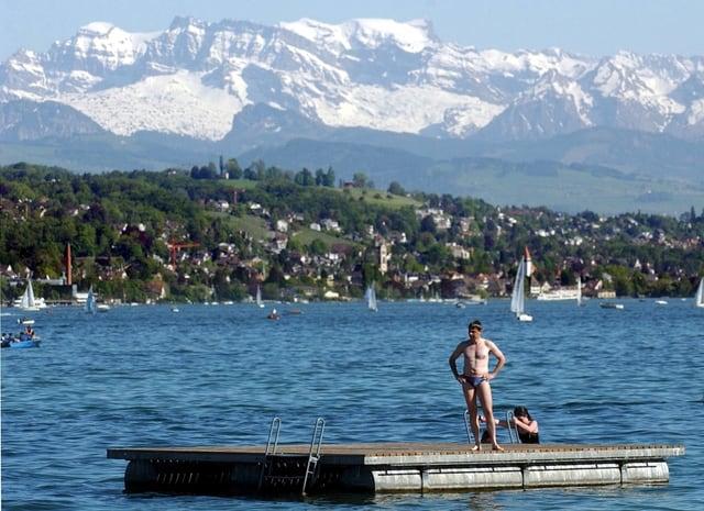 See mit Floss im Vordergurnd. Darauf steht ein Mann in Badehose. Auf dem See sind noch Segelschiffe unterwegs. Im Hintergrund Schneeberge.