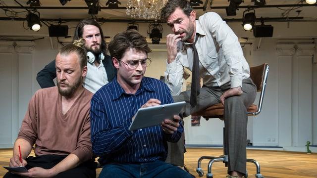 Die vier Schauspieler stecken die Köpfe zusammen und beraten.