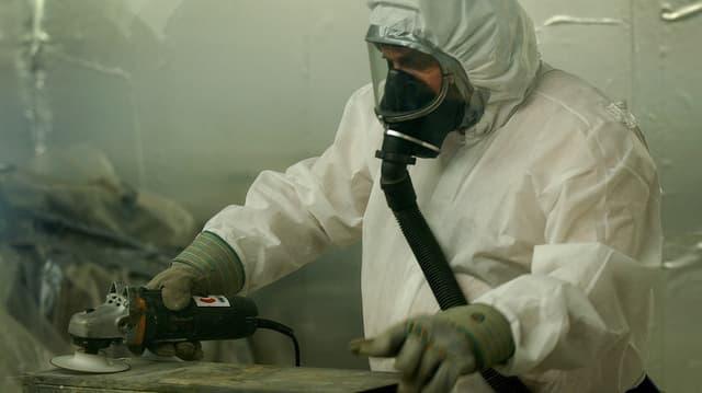 In um en vestgì da protecziun alv e cun mascra da fladar dismetta asbest