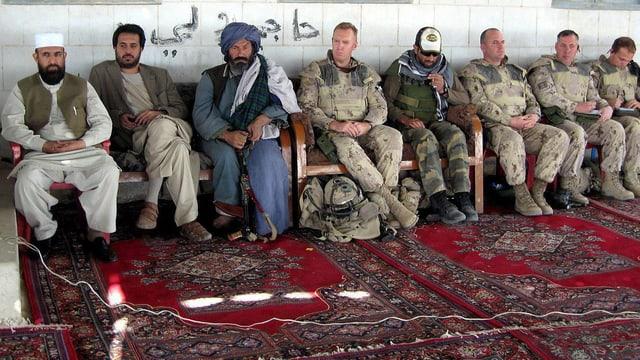 Männer sitzen auf Stühlen, Soldaten und afghanische Stammesführer
