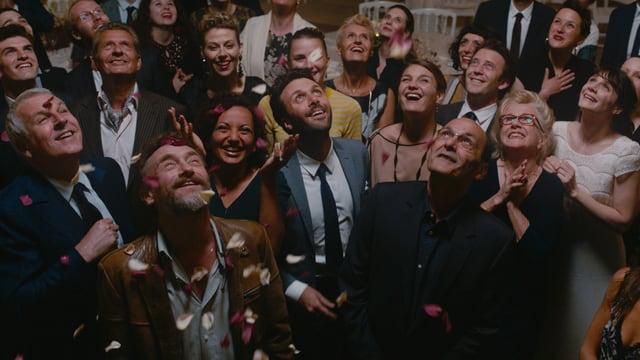 Hochzeitsgäste blicken nach oben, weil Herzen regnen