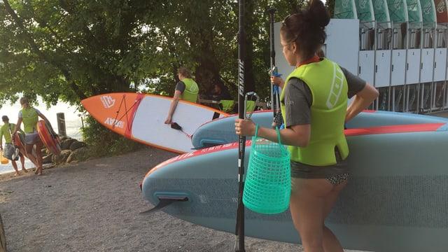 Eine Frau läuft mit einem Stand Up Paddle zum See.