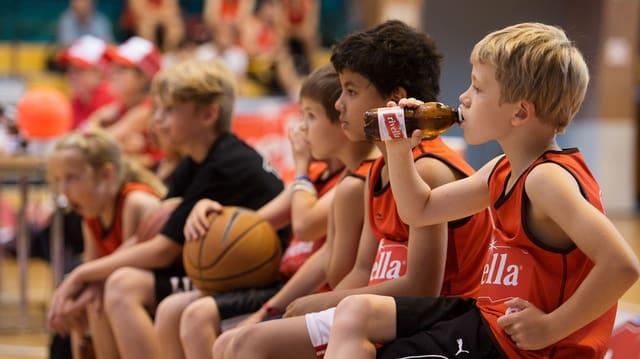 Kinder mit Rivella-Shirts trinken am Rande eines Basketballspiels Rivella.