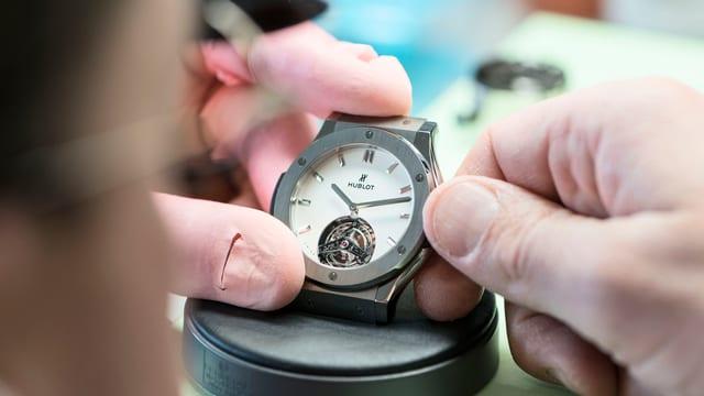 Ein Uhrmacher baut eine Uhr zusammen.