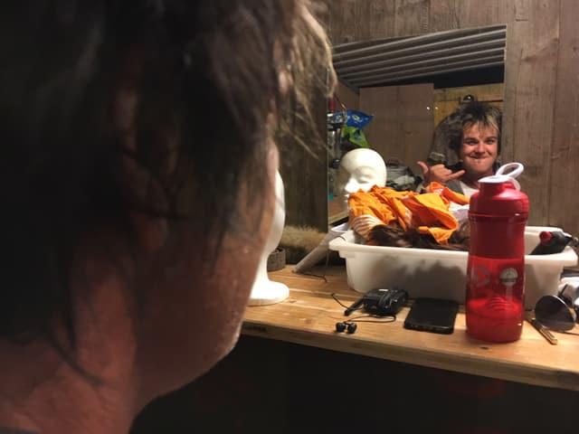 Daniel Bill blickt in den Spiegel und grinst.