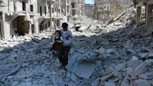 Ein Vater trägt seine Tochter durch die Trümmer der Stadt Aleppo.