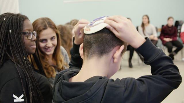 Ein Junge legt sich eine Kippa auf den Kopf.