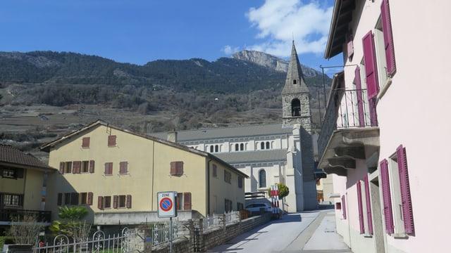 Dorfstrasse mit Kirche im Hintergrund.