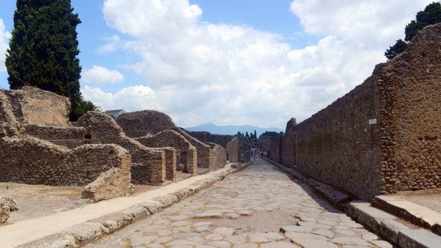 Blick auf eine Strasse mit grossen Steinpflastern, gesäumt von ruinenartigen Mauern.