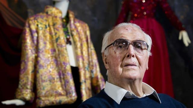 Hubert de Givenchy im Portrait. Dahinter Kleider.